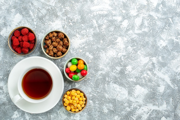 Bovenaanzicht verschillende snoepjes met noten en kopje thee op witte ruimte