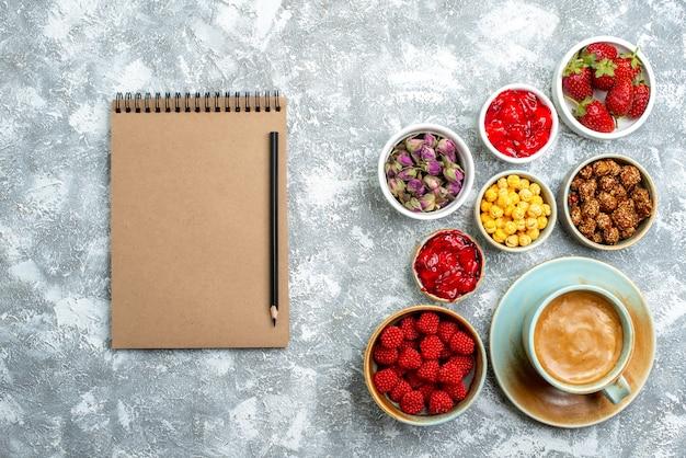 Bovenaanzicht verschillende snoepjes met noten, fruit en koffie op witte ruimte