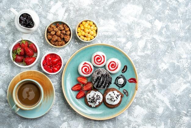 Bovenaanzicht verschillende snoepjes met noten, koffie en koekjes op witte ruimte