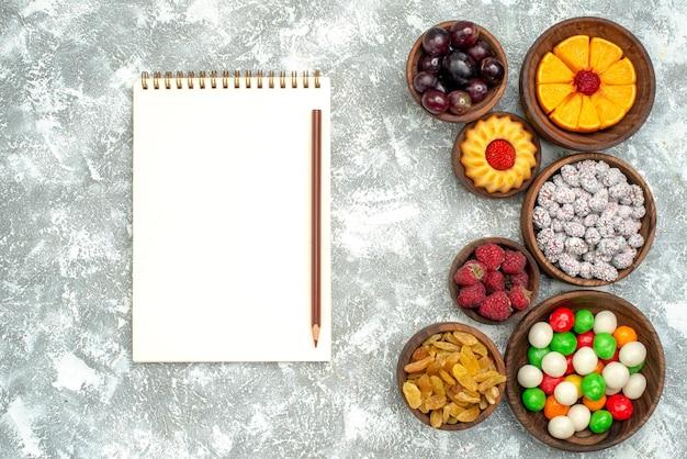 Bovenaanzicht verschillende snoepjes met rozijnen en fruit op witte achtergrond fruitcake kandijsuiker