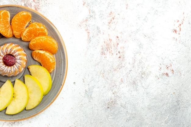 Bovenaanzicht verschillende soorten fruit samenstelling vers en gesneden fruit met cake op lichte witte achtergrond zacht rijp fruit kleur gezondheid