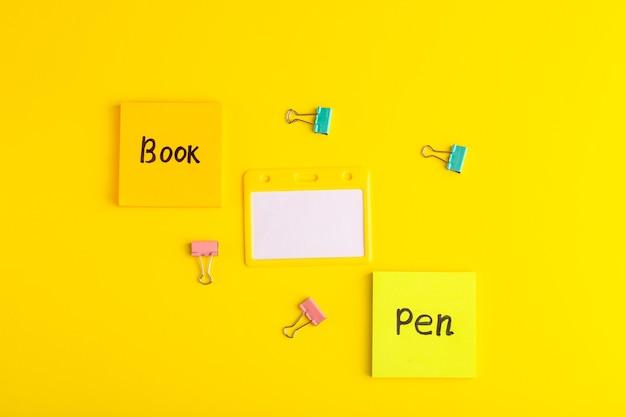Bovenaanzicht verschillende stickers met geschriften op het gele bureau