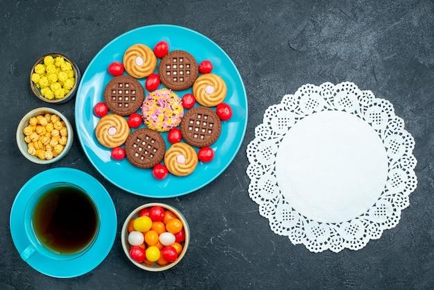 Bovenaanzicht verschillende suikerkoekjes met snoepjes en kopje thee op grijze vloer kandijsuiker zoete thee koekjeskoekje