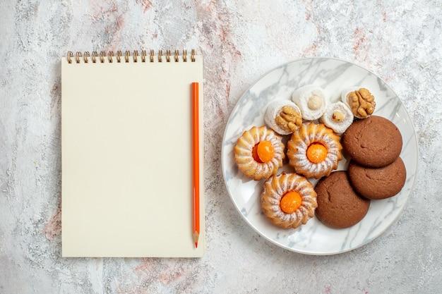 Bovenaanzicht verschillende taarten kleine snoepjes op lichte witte achtergrond cookie biscuit suiker thee zoete cake