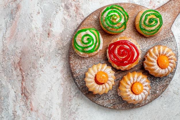 Bovenaanzicht verschillende taarten kleine snoepjes op witte achtergrond cookie biscuit suiker thee zoete cake