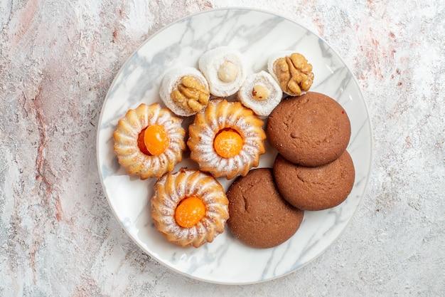 Bovenaanzicht verschillende taarten kleine snoepjes op witte achtergrond cookies biscuit suiker thee zoete cake