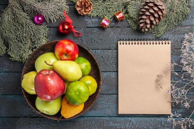 Bovenaanzicht verschillende vers fruit binnen plaat op donkerblauw bureau fruit kleur samenstelling vers rijp