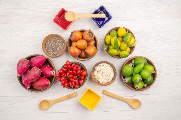 Bovenaanzicht verschillende vers fruit binnen platen op de witte achtergrond rijp exotisch gezond leven tropische kleur dieet