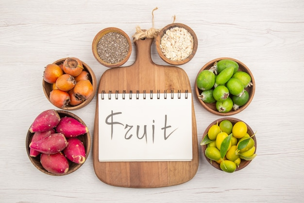 Bovenaanzicht verschillende vers fruit binnen platen op de witte achtergrond tropische rijpe exotische gezonde levenskleur dieet