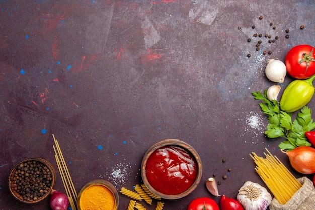 Bovenaanzicht verschillende verse groenten met rauwe pasta op donkere achtergrond rijpe salade verse maaltijd