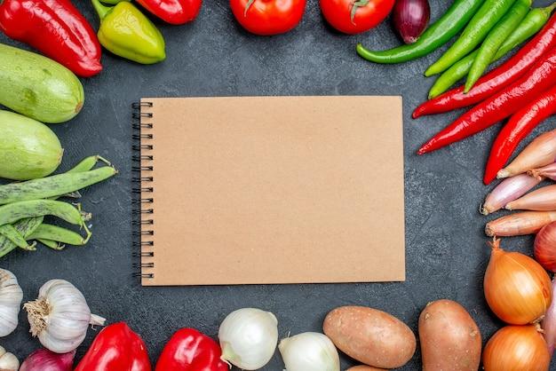 Bovenaanzicht verschillende verse groenten op donkere tafel groente frisse kleurensalade