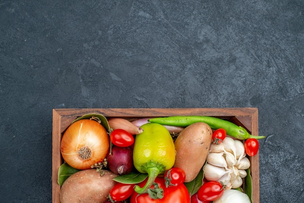 Bovenaanzicht verschillende verse groenten op donkere tafel kleur groenten verse salade rijp