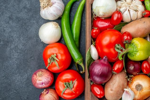 Bovenaanzicht verschillende verse groenten op donkere tafel salade groente vers rijp