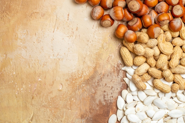 Bovenaanzicht verschillende verse noten met witte zaden op houten bureaunoot veel samenstelling
