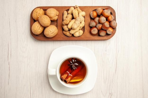 Bovenaanzicht verschillende verse noten pinda's hazelnoten en walnoten met thee op witte bureaunoot snack veel planten