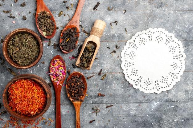 Bovenaanzicht verschillende verse thee gedroogde smaken op grijze ruimte
