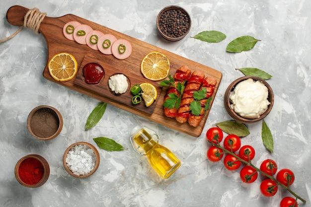 Bovenaanzicht verschillende voedselsamenstelling worstjes met verse tomaten, kruiden, olie en citroenen op lichte tafel maaltijd voedsel veegtable kleurenfoto