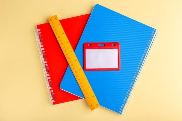 Bovenaanzicht verschillende voorbeeldenboeken blauw en rood met liniaal op lichtgeel oppervlak