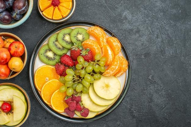 Bovenaanzicht verschillende vruchten samenstelling vers en rijp op de donkere achtergrond zacht vers fruit gezondheid rijp