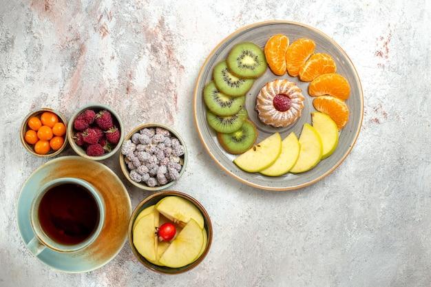 Bovenaanzicht verschillende vruchten samenstelling vers fruit met cake en kopje thee op witte achtergrond zachte vruchten rijpe vitamine gezondheid
