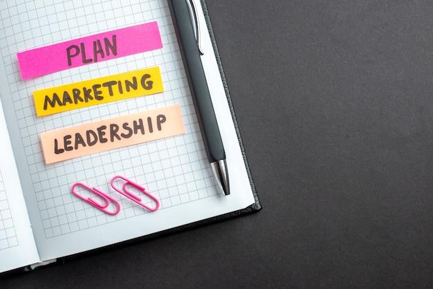 Bovenaanzicht verschillende zakelijke notities in blocnote op donkere achtergrond business plan job teamwork leiderschap marketing strategie kantoorwerk