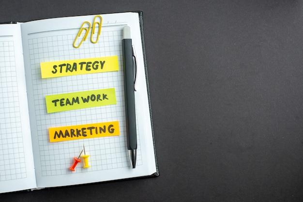 Bovenaanzicht verschillende zakelijke notities in blocnote op donkere achtergrond businessplan baan teamwerk leiderschap strategie werk marketing vrije ruimte