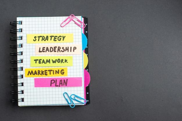 Bovenaanzicht verschillende zakelijke notities in blocnote op donkere achtergrond zakelijk werk teamwerk marketing leiderschap plan kleur vrije ruimte