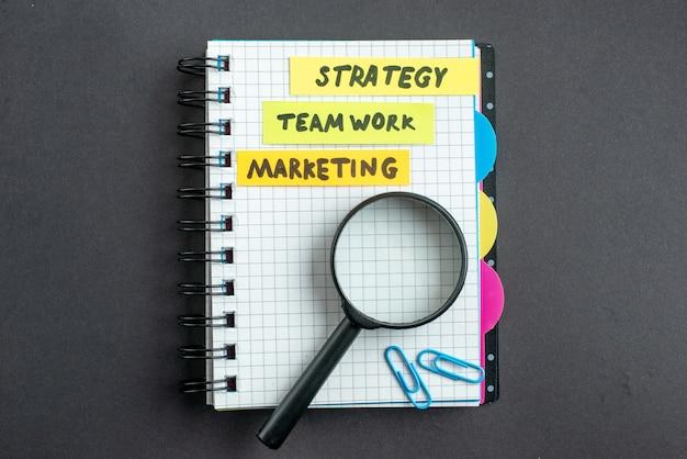 Bovenaanzicht verschillende zakelijke notities in blocnote op donkere ondergrond zakelijk werk teamwerk marketing leiderschap plan strategiewerk