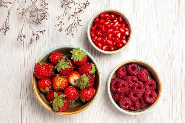 Bovenaanzicht verse aardbeien met frambozen en granaatappels op witte bureaubes vers fruit zacht rijp wild