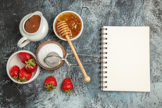 Bovenaanzicht verse aardbeien met honing op het donkere oppervlak fruit bessen zoet