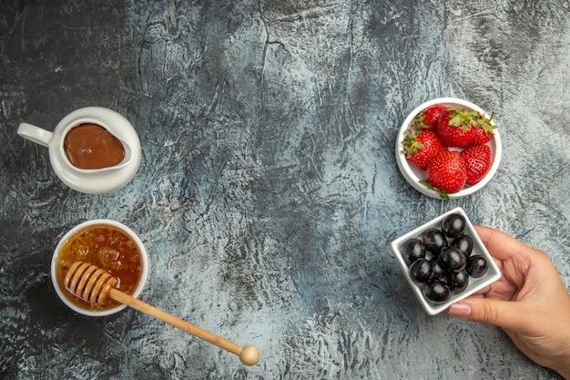 Bovenaanzicht verse aardbeien met olijven en honing op donkere oppervlakte bes zoet fruit