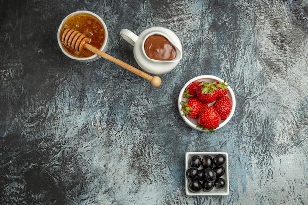 Bovenaanzicht verse aardbeien met olijven en honing op donkere oppervlakte zoete fruitbes