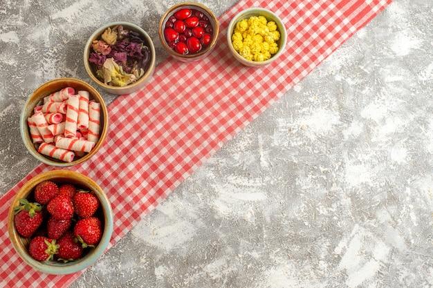 Bovenaanzicht verse aardbeien met snoepjes op wit oppervlak snoep zoet fruit