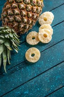 Bovenaanzicht verse ananas die gedroogde ananasringen op blauwe achtergrond legt