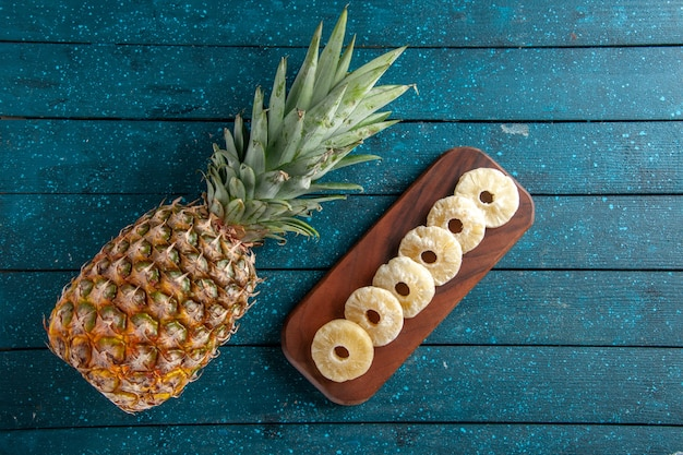 Bovenaanzicht verse ananas en droge ananasschijfjes op een houten bord op blauwe houten achtergrond