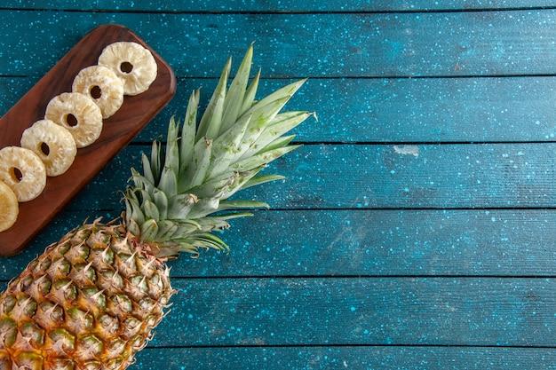 Bovenaanzicht verse ananas en droge ananasschijfjes op een houten bord op een blauwe houten achtergrondkopieerplaats