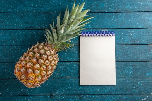 Bovenaanzicht verse ananas en notitieblok op blauwe houten achtergrond