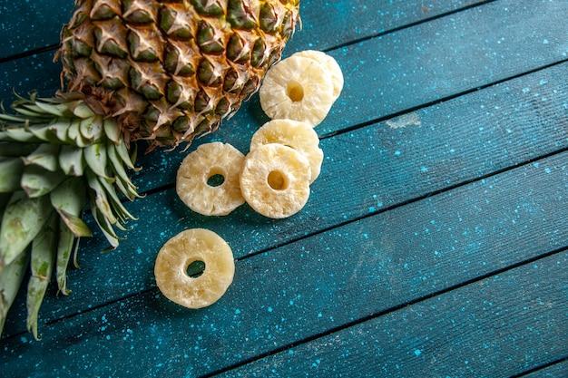 Bovenaanzicht verse ananas met gedroogde ananasringen op blauwe houten achtergrond vrije ruimte