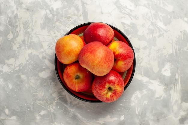 Bovenaanzicht verse appels binnen plaat op wit oppervlak