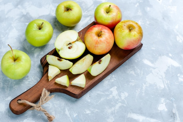 Bovenaanzicht verse appels gesneden hele vruchten op het lichtwitte oppervlak