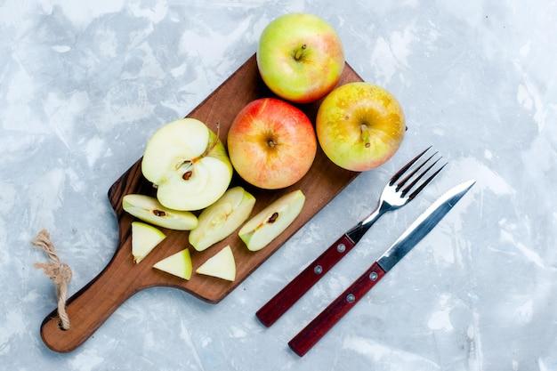 Bovenaanzicht verse appels in plakjes en hele vruchten op het lichtwitte bureau