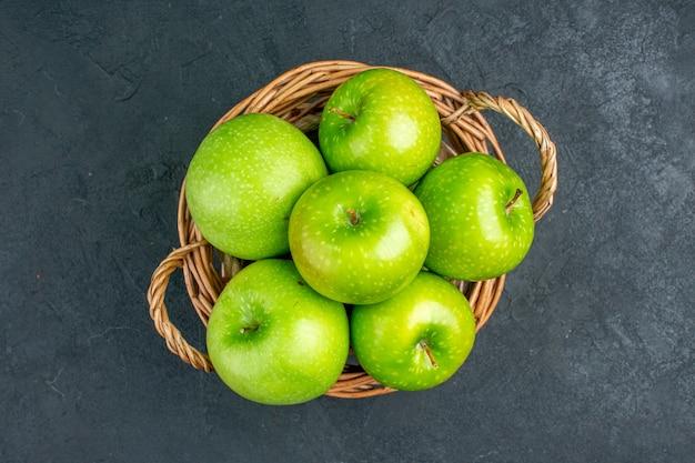 Bovenaanzicht verse appels in rieten mand op donkere oppervlakte vrije ruimte