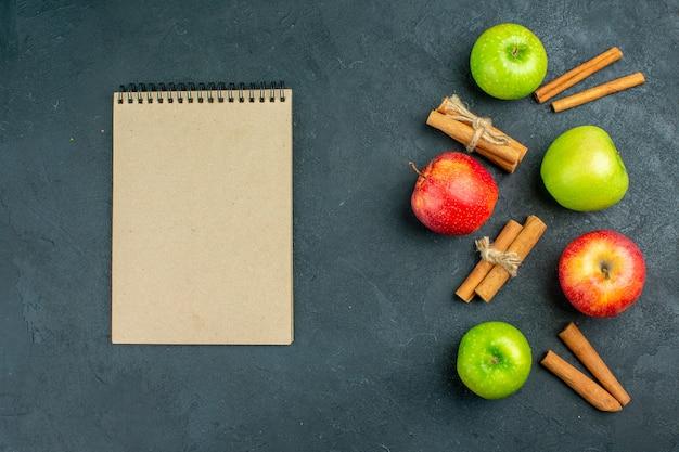 Bovenaanzicht verse appels kaneelstokjes notebook op donkere ondergrond