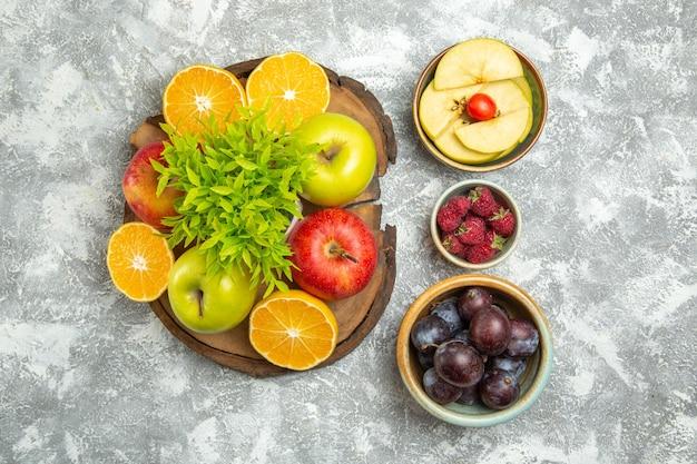 Bovenaanzicht verse appels met gesneden sinaasappelen en pruimen op witte achtergrond rijp zacht fruit verse appel