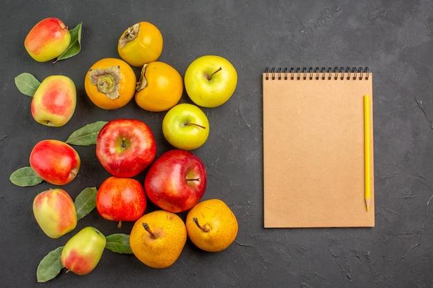 Bovenaanzicht verse appels met kaki en peren op donkere tafel zachte verse rijpe boom