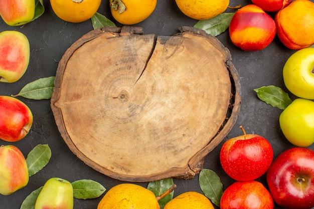 Bovenaanzicht verse appels met peren en kaki op donkere bureau zachte rijpe verse boom