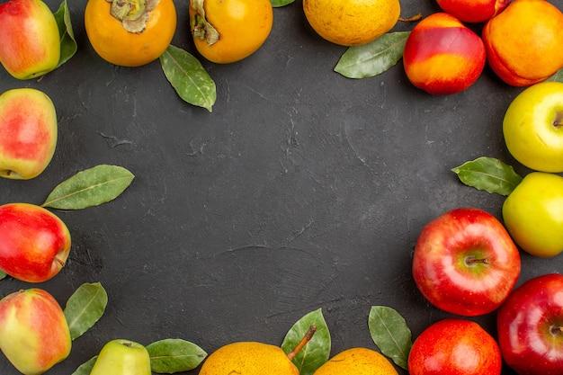 Bovenaanzicht verse appels met peren en kaki op een donkere tafel zacht rijp vers