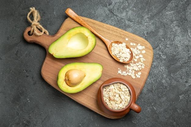 Bovenaanzicht verse avocado met rauwe granen op een grijs oppervlak fruit exotisch ontbijt vers
