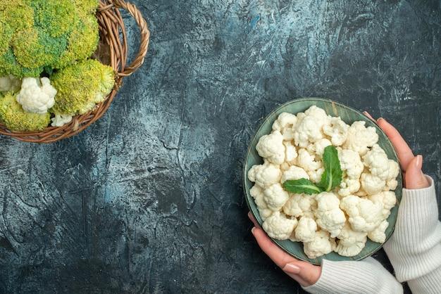 Bovenaanzicht verse bloemkool in mand en bord op de lichtgrijze tafel