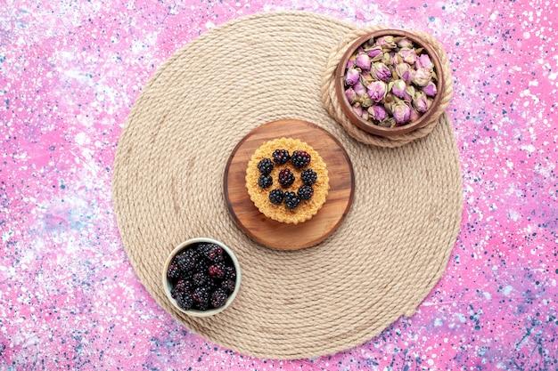 Bovenaanzicht verse bramen in witte kleine pot met kleine cake op het roze bureau.